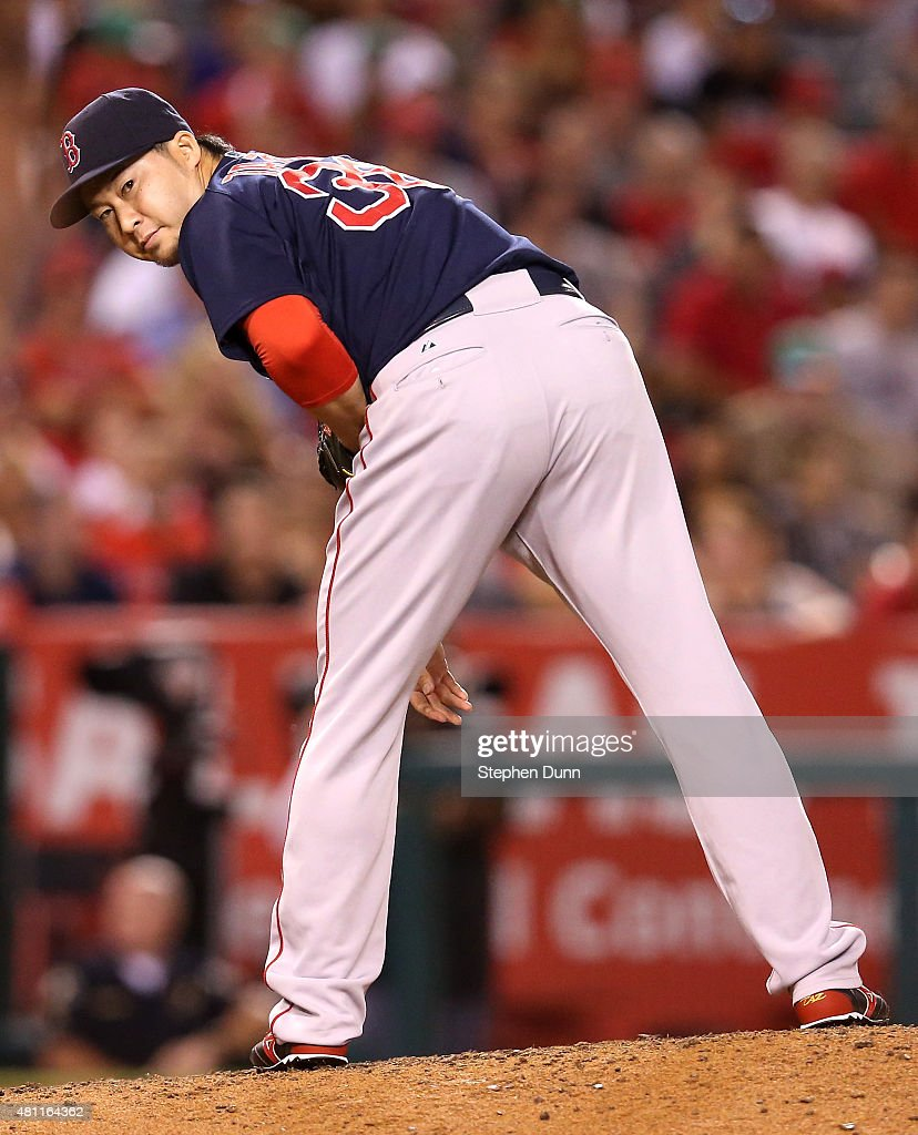 Reliever Junichi Tazawa #36 of the Boston Red Sox checks a runner at first in the eighth inning against the Los Angeles Angels of Anaheim at Angel Stadium of Anaheim on July 17, 2015 in Anaheim, California.