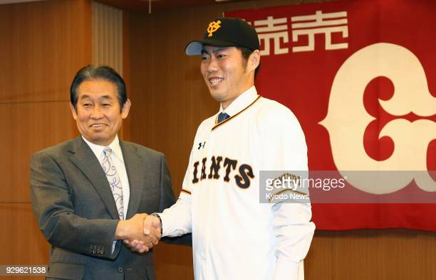 Reliever Koji Uehara and Yoshitaka Katori the Yomiuri Giants general manager shake hands during a press conference in Tokyo on March 9 as Uehara...