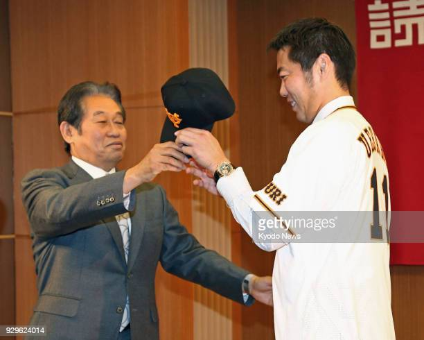 Reliever Koji Uehara receives a cap from Yoshitaka Katori the Yomiuri Giants general manager during a press conference in Tokyo on March 9 as Uehara...