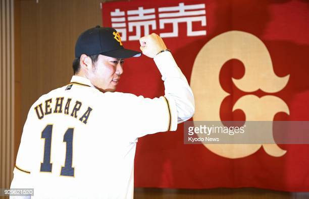 Reliever Koji Uehara wearing his No 11 jersey poses for photos at a press conference in Tokyo on March 9 as he rejoins his first pro club the Yomiuri...