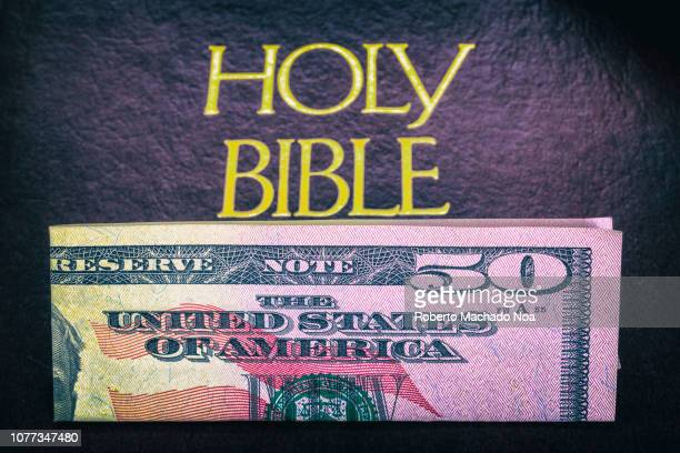 Religion and money A 50 US dollar bill lays on top of the cover of a Holy Bible