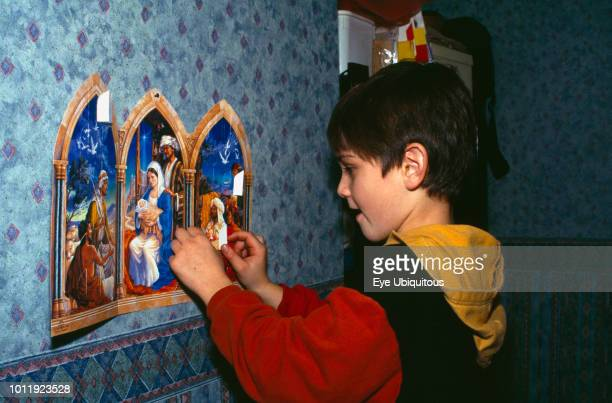 Religion, Christianity, Boy opening the windows on an Advent Calendar.