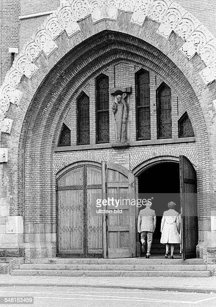 religion Christianity church goers older man and older woman walk to the church service aged 60 to 70 years church portal SaintBavoChurch...
