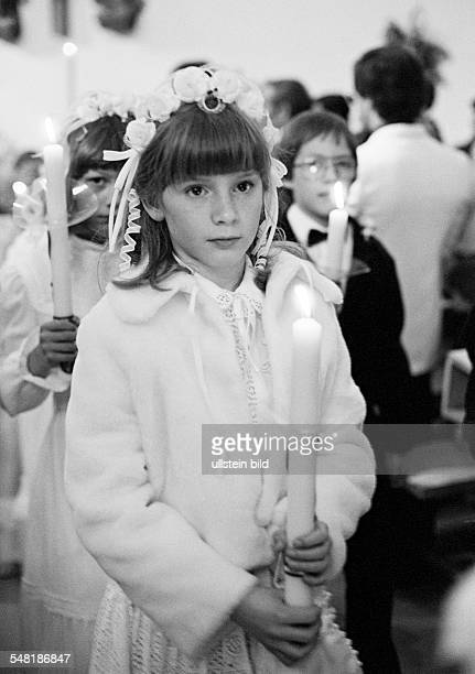 religion Christianity First Communion during the procession to the church girls and boys hold communion candles in the hands aged 8 to 12 years