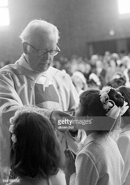 religion Christianity First Communion Eucharistic mass priest administers the Holy Communion to a girl aged 8 to 12 years aged 55 to 65 years Babette