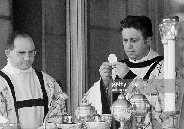 religion Christianity holy mass Eucharist priest holds the communion wafer aside an acolyte aged 40 to 50 years