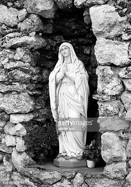 religion Christianity praying Virgin Mary sculpture in a grotto mother of Jesus sculpture Germany North RhineWestphalia Westphalia Sauerland