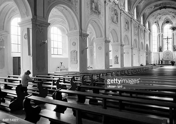 religion Christianity young woman kneels in a pew and prays aged 30 to 35 years Elisabeth