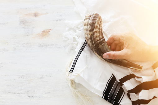 religion image of shofar (horn) on white prayer talit. Rosh hashanah (jewish New Year holiday), Shabbat and Yom kippur concept 1172842171
