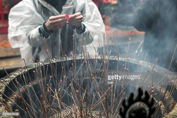 Religion in China: An Asian Buddhist Worshiper Offering a Lighting Stick for Praying in Front of Burning Incense Burner, Censer with Inclined, Oblique Light