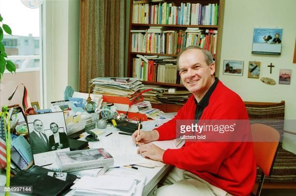 Religionswissenschaftler Fernsehmoderator Autor D Porträt am Schreibtisch in seiner Wohnung in Mainz