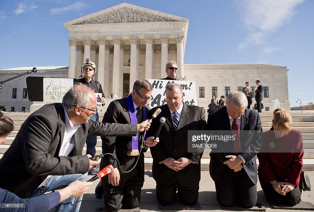 Religious activists pray following oral arguments in the case of Town of Greece v. Galloway dealing with prayer in government, outside the Supreme Court in Washington, DC, on November 6, 2013. The case deals with whether holding a prayer prior to the monthly public meetings in the New York town of Greece violates the Constitution by endorsing a single faith. AFP PHOTO / Saul LOEB