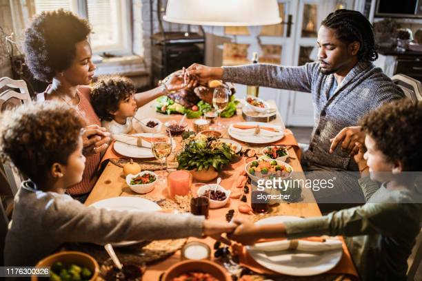 religious black family saying grace before thanksgiving lunch at home. - gratitude stock pictures, royalty-free photos & images
