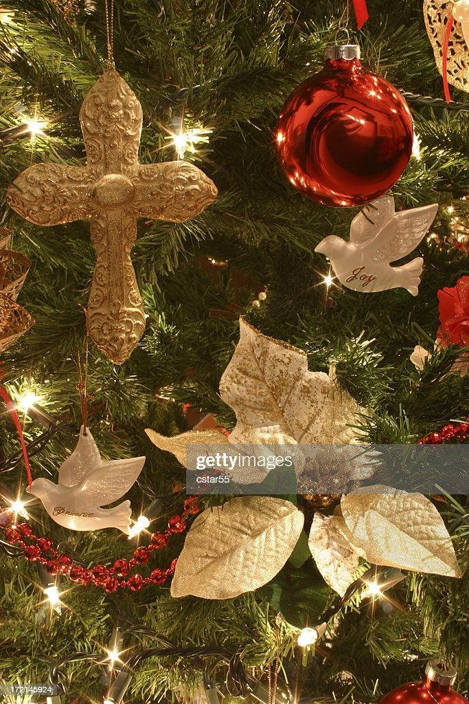 religious christmas cross hanging on tree with other ornaments stock photo