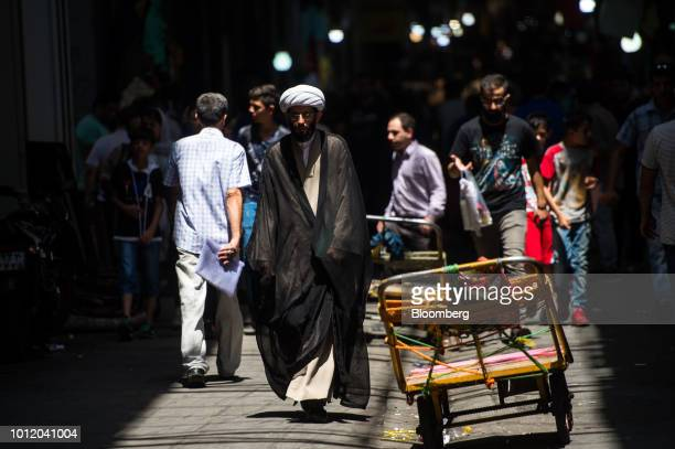 A religious cleric passes traders trolleys inside the Grand Bazaar in Tehran Iran on Monday Aug 6 2018 Irans central bank acting on the eve of US...