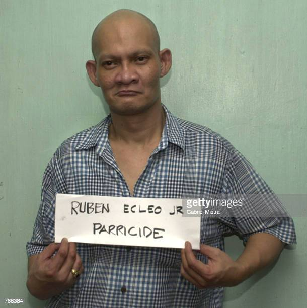 Religious cult leader Ruben Ecleo Jr holds a sign with his name on it as well as the name of his crime 'parracide' as he is photographed inside...