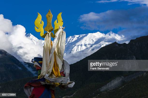 Religious elements on the roof of Braga Gompa, the mountain Annapurna 2 in the distance.