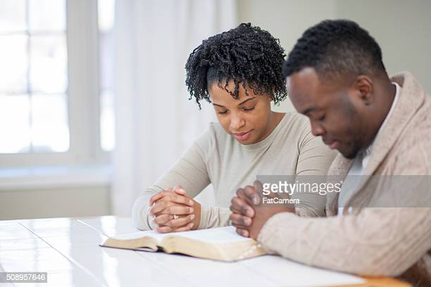 religious ethnic couple praying with a bible - praying stock pictures, royalty-free photos & images