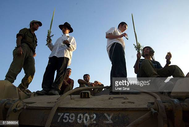 Religious Israelis welcome an army Armored Personnel Carrrier returning for rest from the Gaza Strip with the four plants of Sukkot the Jewish feast...