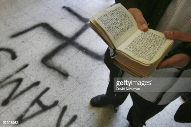 A religious Jew recites prayers over a Swastika that desecrates the floor of the Grand Synagogue May 4 2006 in Petah Tikva in central Israel Jewish...