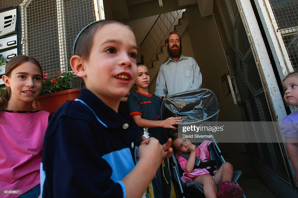 A religious Jewish family gathers at the entrance to their settlement in the Arab neighborhood of Abu Tor August 18, 2008 in East Jerusalem, Israel. The settlement, an apartment building which houses a number of families, is a former Arab home purchased by the Ateret Cohanim organization, which is dedicated to expanding Jewish settlement in East Jerusalem, the half of the city that Israel captured from Jordan in the 1967 Six Day War.