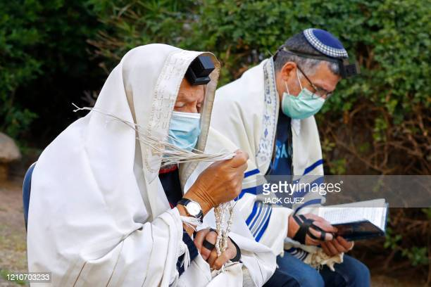 A religious Jewish man wearing the talit a traditional Jewish prayer shawl and on his forehead the tefillin a small black leather box containing...