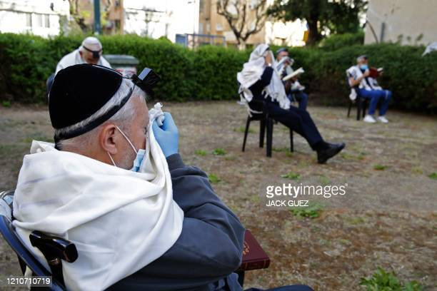 Religious Jewish men wearing the talit a traditional Jewish prayer shawl and on their foreheads the tefillin a small black leather box containing...