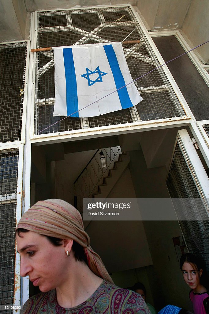 A religious Jewish woman steps out of the entrance to her settlement in the Arab neighborhood of Abu Tor August 18, 2008 in East Jerusalem, Israel. The settlement, an apartment building which houses a number of families, is a former Arab home purchased by the Ateret Cohanim organization, which is dedicated to expanding Jewish settlement in East Jerusalem, the half of the city that Israel captured from Jordan in the 1967 Six Day War.