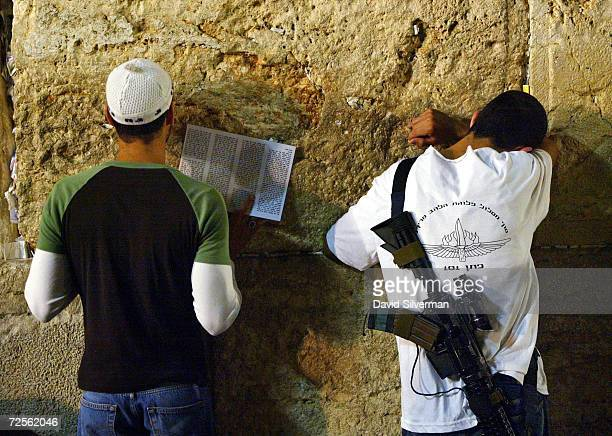 Religious Jews one an Israeli soldier pray before dawn at the Western Wall in Jerusalem's Old City during the annual 9th of Av memorial for the...