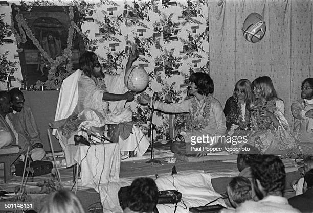 Religious leader Maharishi Mahesh Yogi presents Beatle George Harrison with an upsidedown globe of the world at a party to celebrate the musician's...