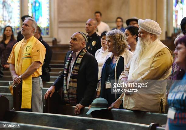 Religious leaders from up to a dozen different faiths listen to a service during the 'Interfaith Solidarity March Los Angeles 2018' event to denounce...
