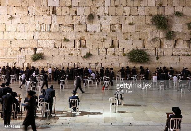 Religious men pray in front of the Western Wall, also called the Wailing Wall, located in the Old City of Jerusalem, Israel.