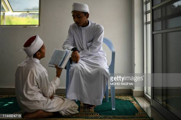 Religious Muslim students read and memorise the Koran at a seminary during the Islamic holy fasting month of Ramadan in Bentong outside Kuala Lumpur...