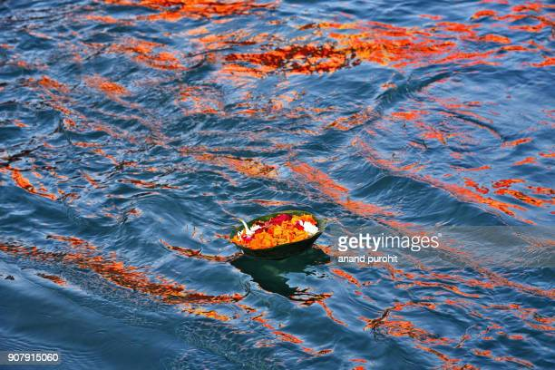 Religious offerings and floating diyas (indian lamp) with flowers floating on water of holy river Ganga at Haridwar, Uttarakhand, India