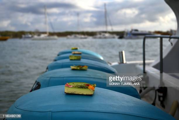 Religious offerings are seen placed on the outboard motors of a fast boat before leaving for a trip to Nusa Penida island from Serangan island in...