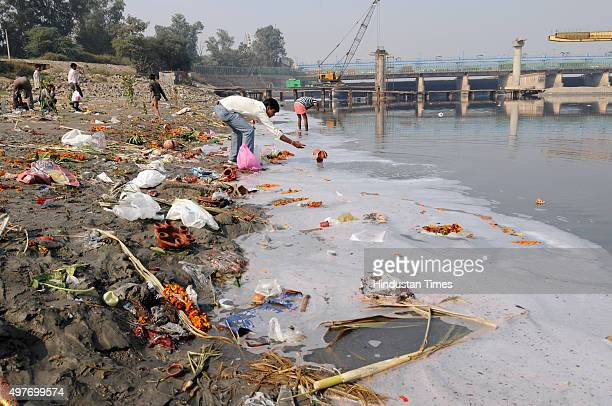 Religious offerings from devotees and leftover wooden frames earthen lamps and other pile up on the banks of Yamuna river after the end of Chhath...