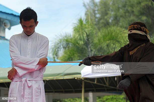 A religious officer canes an Acehnese man 100 times for having sex outside marriage which is against Sharia law in Banda Aceh on November 28 2016...