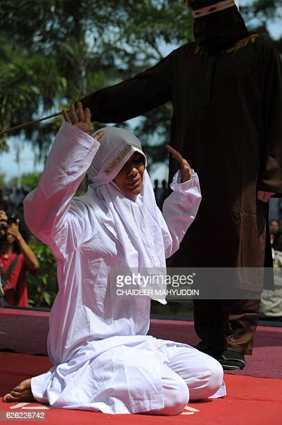 A religious officer canes an Acehnese woman for spending time in close proximity with a man who is not her husband which is against Sharia law in...