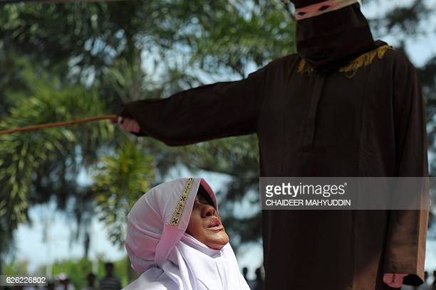 TOPSHOT A religious officer canes an Acehnese woman for spending time in close proximity with a man who is not her husband which is against Sharia...