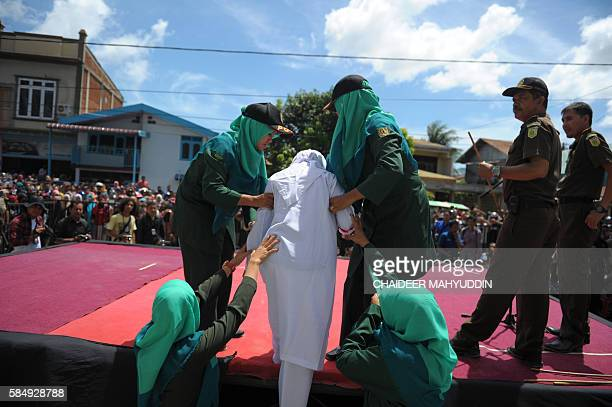 Religious officers bring an Acehnese youth onstage before a public caning event as punishment for dating outside of marriage which is against sharia...