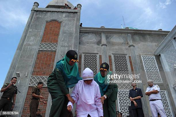 Religious officers hold an Acehnese youth onstage before a public caning event as punishment for dating outside of marriage which is against sharia...