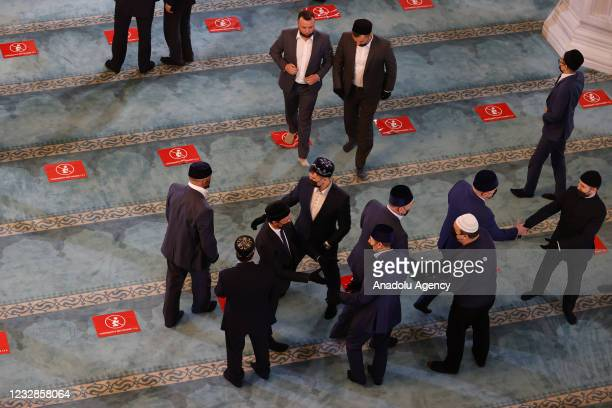 Religious officials greet each other after performing Eid al-Fitr prayer at the Moscow Central Mosque within precautions against the novel...