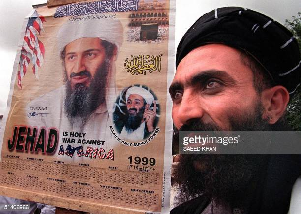 A religious protester holds a portrait of Saudi dissident Osama bin Laden during a protest rally against the United States 30 July 1999 in Islamabad...
