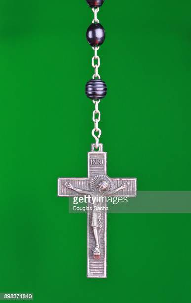 Religious Rosary praying beads on a green background