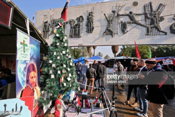 Religious shrine with miniature coffins is ornated with a Christmas tree in the Iraqi capital's Tahrir Square on December 11, 2019. - Since October...