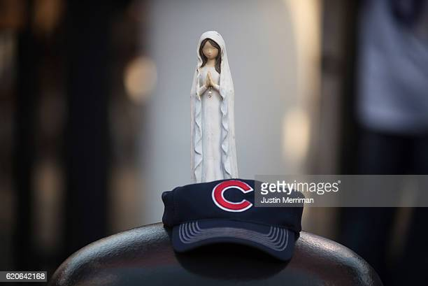 A religious statue stands on top of a Cubs hat in front of Progressive Field before the start of game 7 of the World Series between the Cleveland...