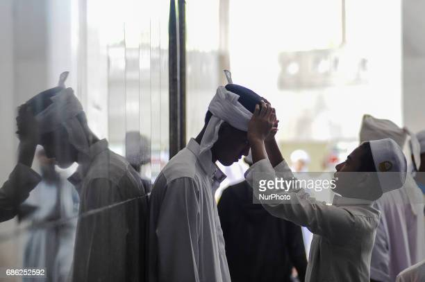 Religious students adjust turban at the corridor of the Federal Territory Mosque during the gathering for students who had successfully memorised the...