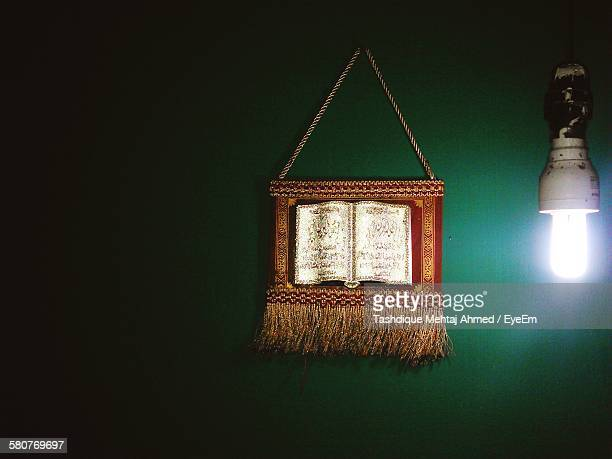 religious text on decor by light bulb hanging from wall - guwahati stock photos and pictures