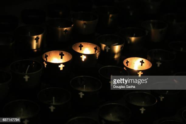 religious votive candles glowing in a dark room - cero foto e immagini stock