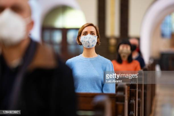 religious woman visiting church during pandemic - place of worship stock pictures, royalty-free photos & images